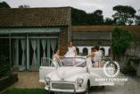 Bride is helped into a car by Bridesmaids