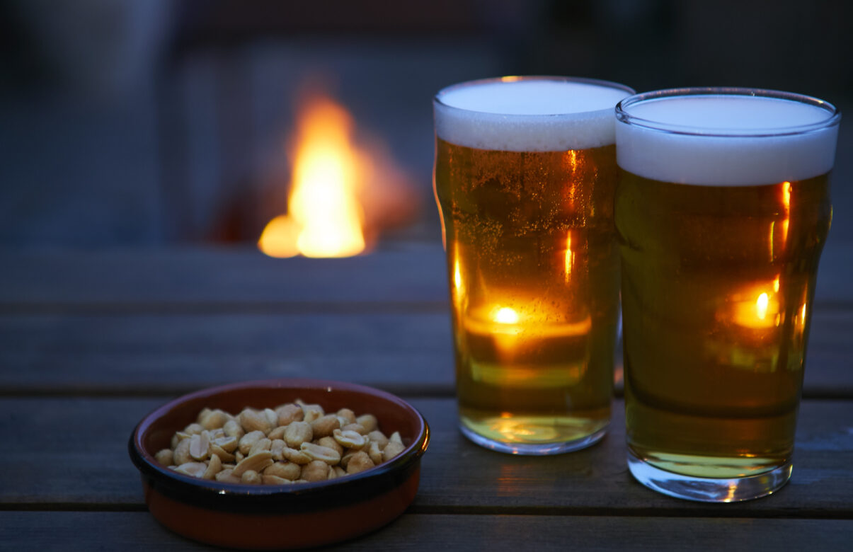 Two pints of beer and a bowl of peanuts