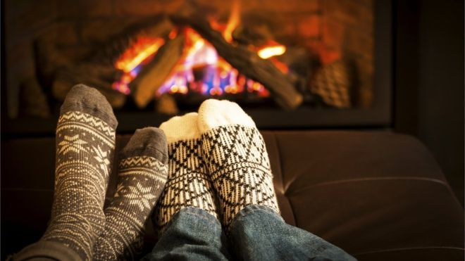 Two people's feet in front of the fireplace