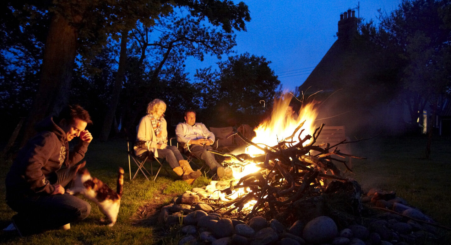 People sitting besides a Fire